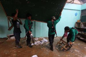 New People's Army regulars help repair a classroom damaged by Typhoon Pablo in 2012.